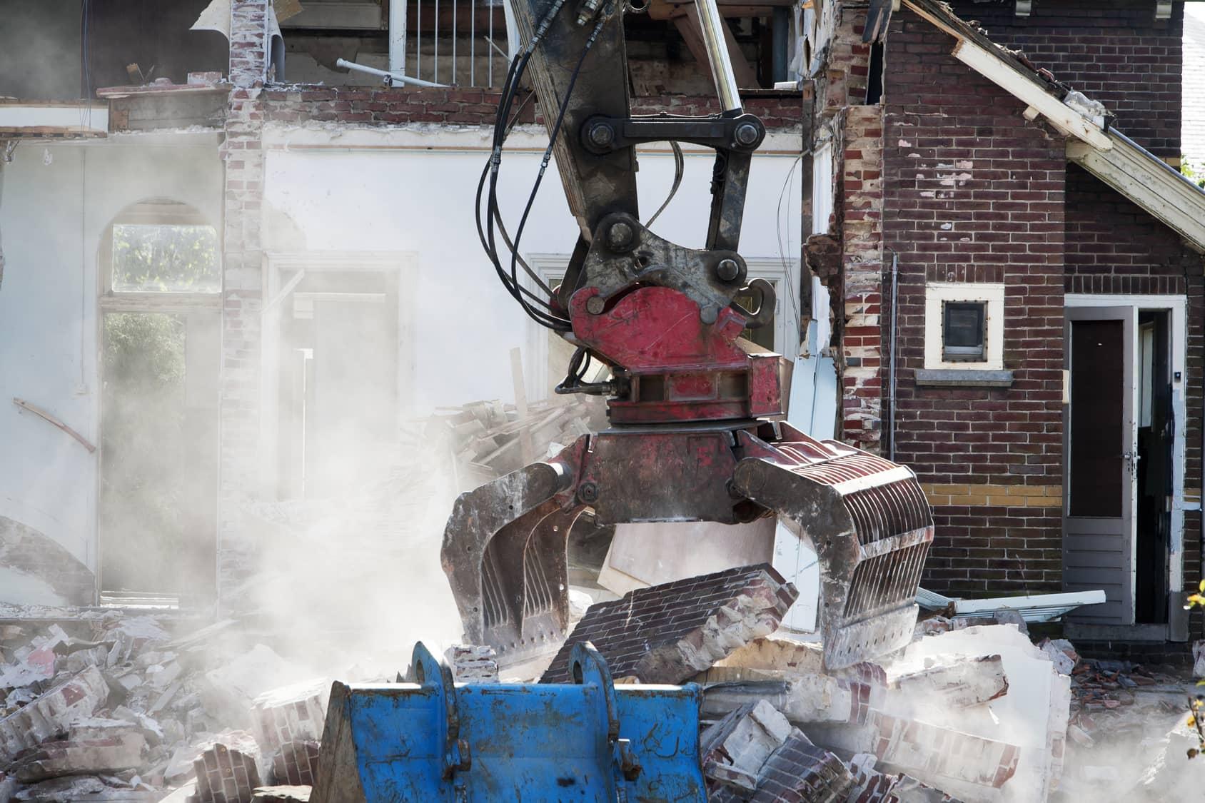 Demolishing an abandoned house with a grab